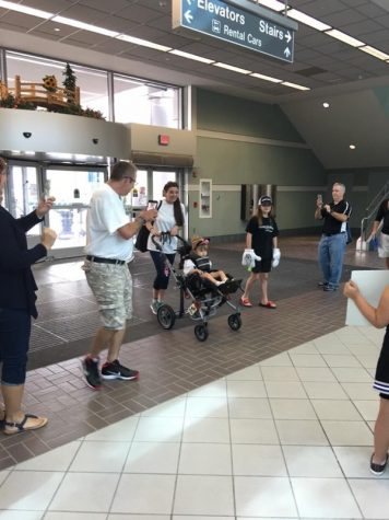 Make-a-Wish recipient Alia and her mom arrive at the airport to find signs and cheers from cheerleaders of all ages as part of their send-off to Disney World.