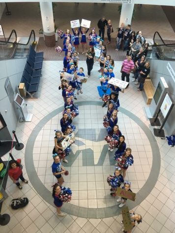 The Londonderry Cheerleaders, ECE cheerleaders, and the Blue Lions wait in the airport for Make-a-Wish-recipient Alia to arrive. The cheerleaders made signs, so Alia's send-off to Disney World would be filled with fun and cheers.