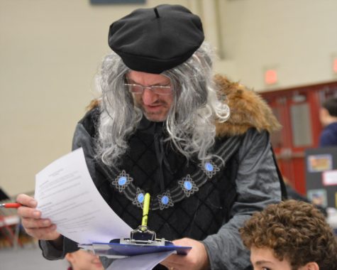 Mr. Willis goes over a student's project dressed in Renaissance attire from head to toe. He worea fur-lined grey and black tunic accessorized witha grey wig on his head and black tights on his legs.