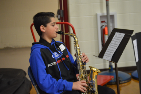 Freshman Tyler Fauc scans his music sheets as he plays his own saxophone.