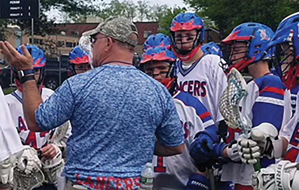 The boys lacrosse team surrounds Coach Sampson prior to their game as he explains various tactics for them to use.