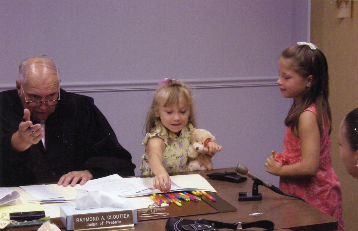 Alyssa and Marissa Neal sit with a judge and sign various documents at their adoption hearing.