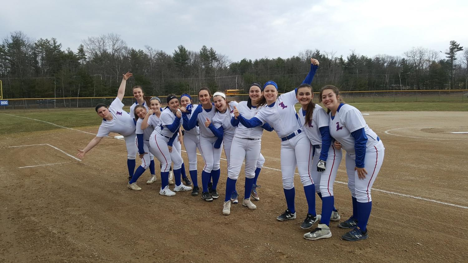 The girls softball team gathering together for a picture at home plate before a home match.