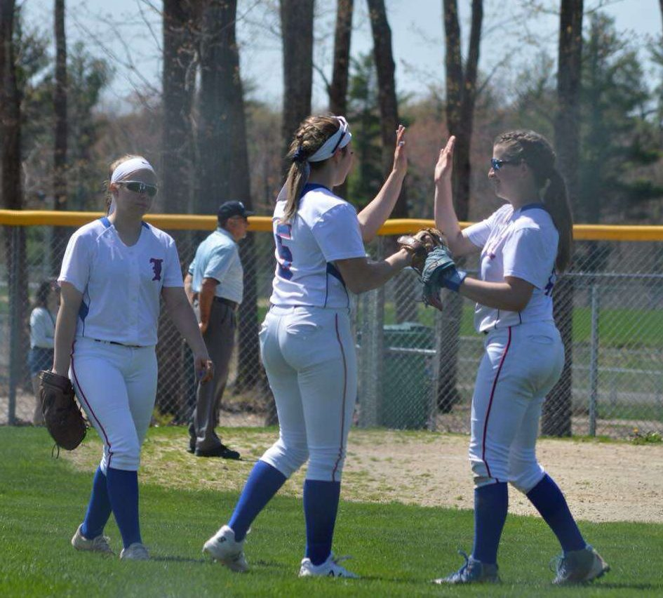 Junior Miranda Galan, Sophomore Gia Komst, and Senior Lauren Misiaszek celebrate in the outfield after a stellar play.