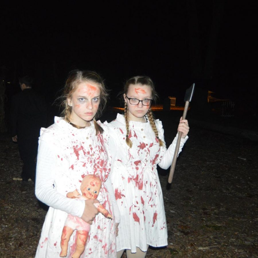 Sophomores+Gabby+Page+and+Evie+Burnette+stare+at+walkers+in+an+attempt+to+scare+them+as+they+travel+through+the+Haunted+Woods+at+last+year%E2%80%99s+performance.+%0A%0A
