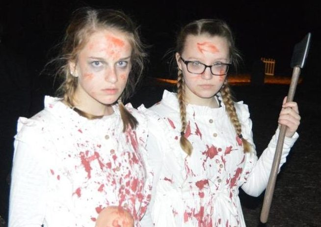 Sophomores Gabby Page and Evie Burnette stare at walkers in an attempt to scare them as they travel through the Haunted Woods at last year's performance.