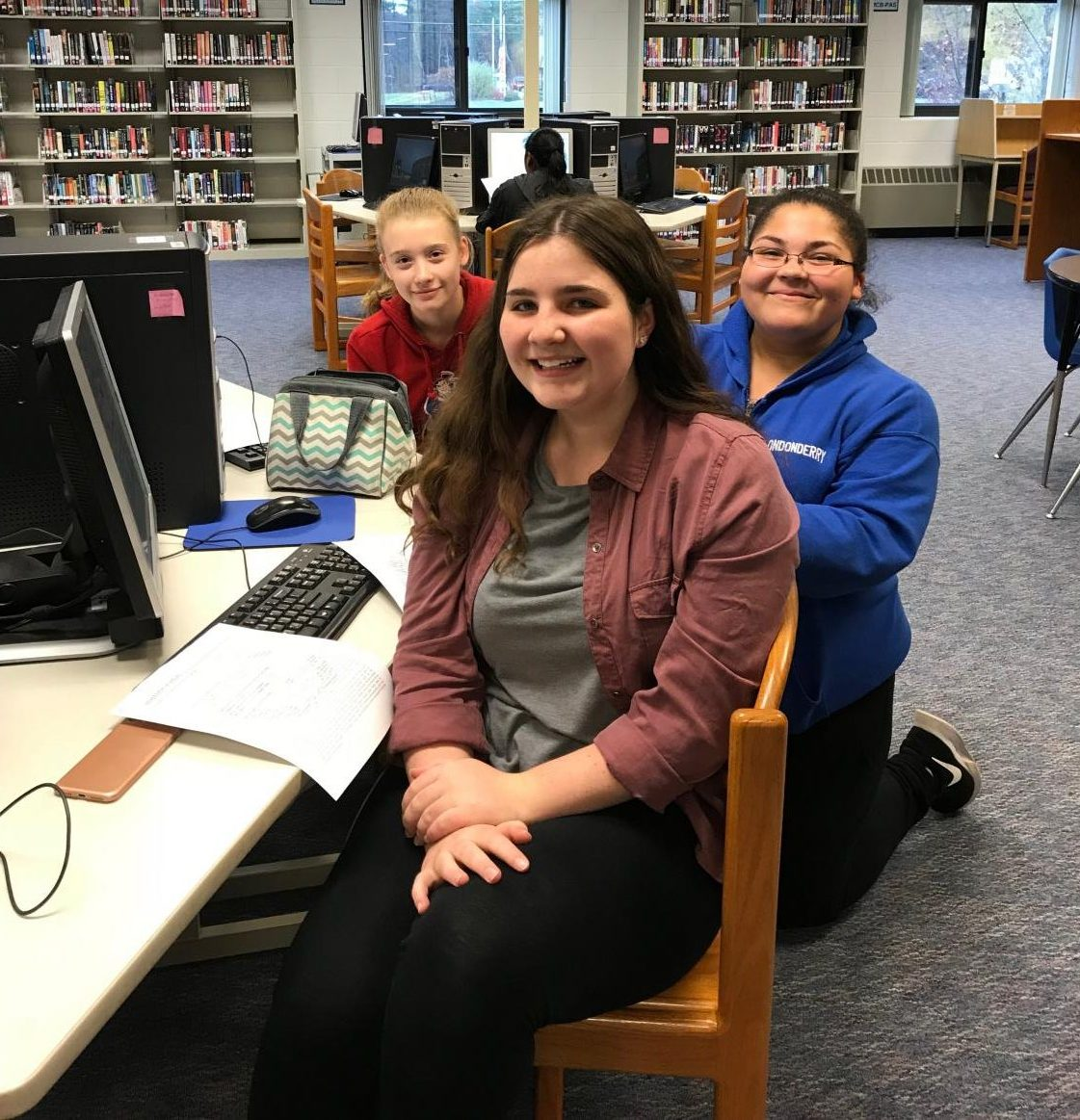 Club members Maya Lincoln, Marie Duffy, and Haley Hines research in the library during a meeting.