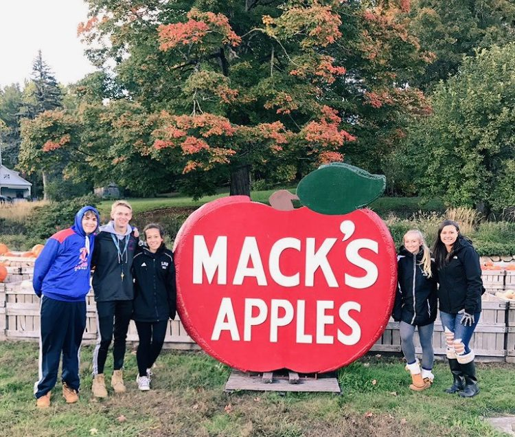 Students from the class of 2020 stand next to the Mack's Apples sign at a recent class event.