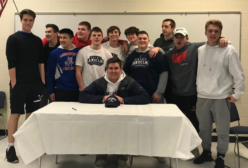 Friends surround Berube as he signs off on his commitment to Saint A's college for football.