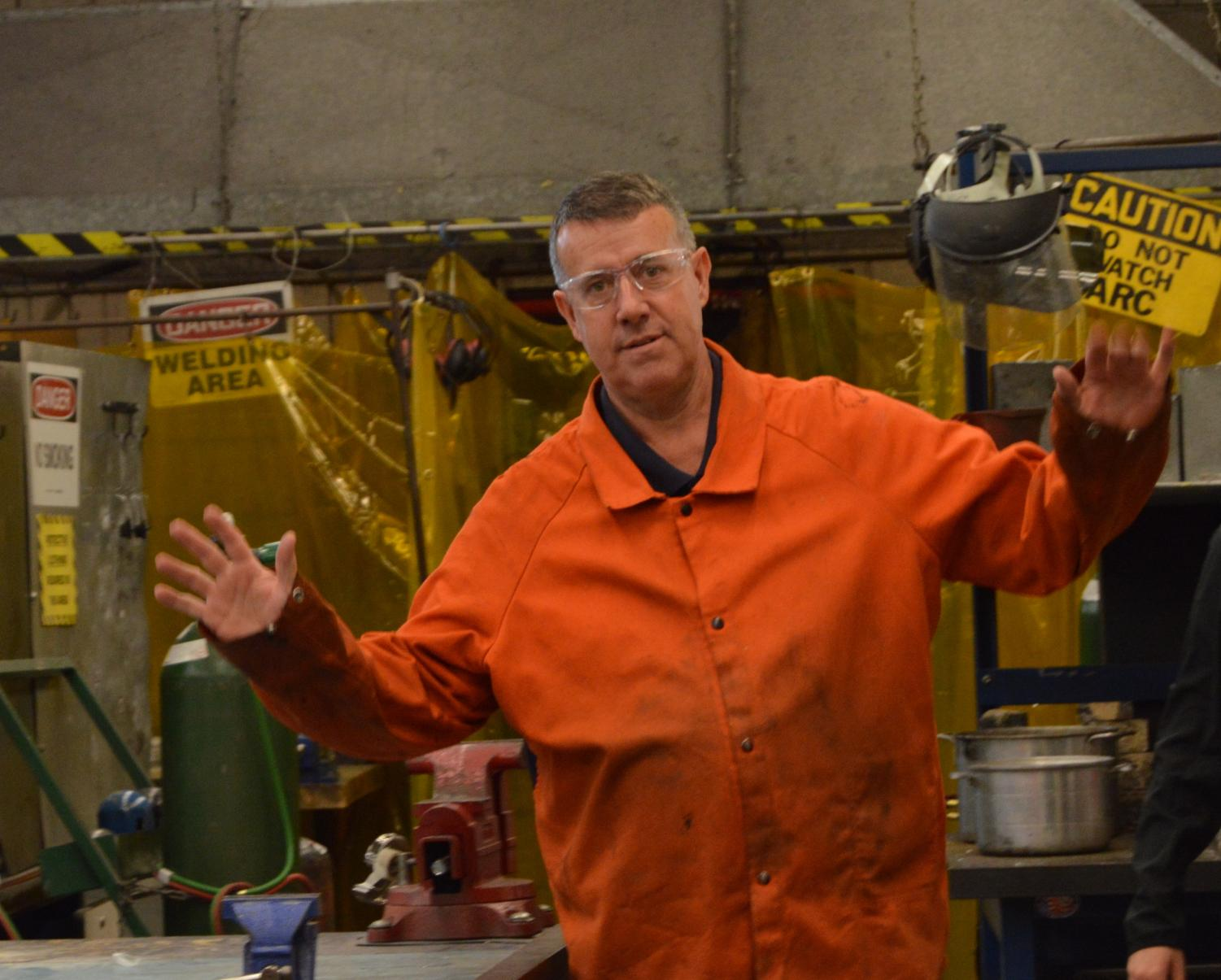 Last year's Teacher of the Year, Mr. Decloux, poses for a photo during his metals class.