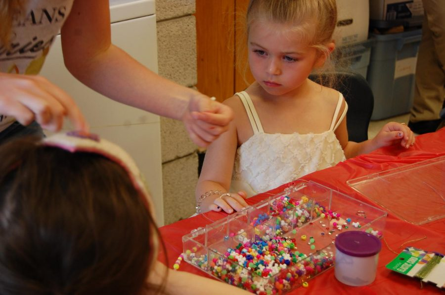 Ainsley watches as she gets taught how to make the perfect bracelet. Her favorite part of the day was