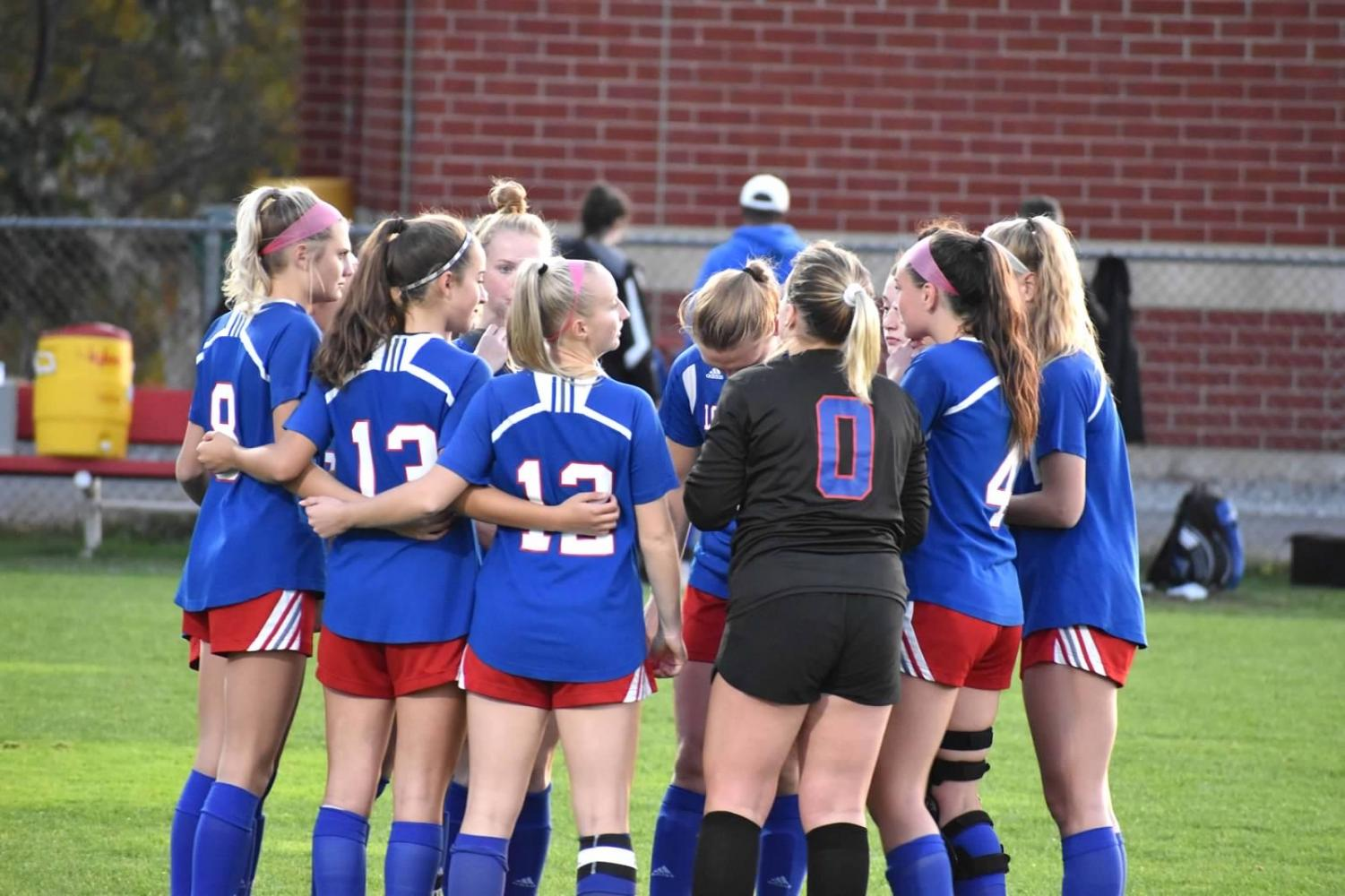 The girls' varsity soccer team gather together to strategize their next play during the recent game against Exeter.