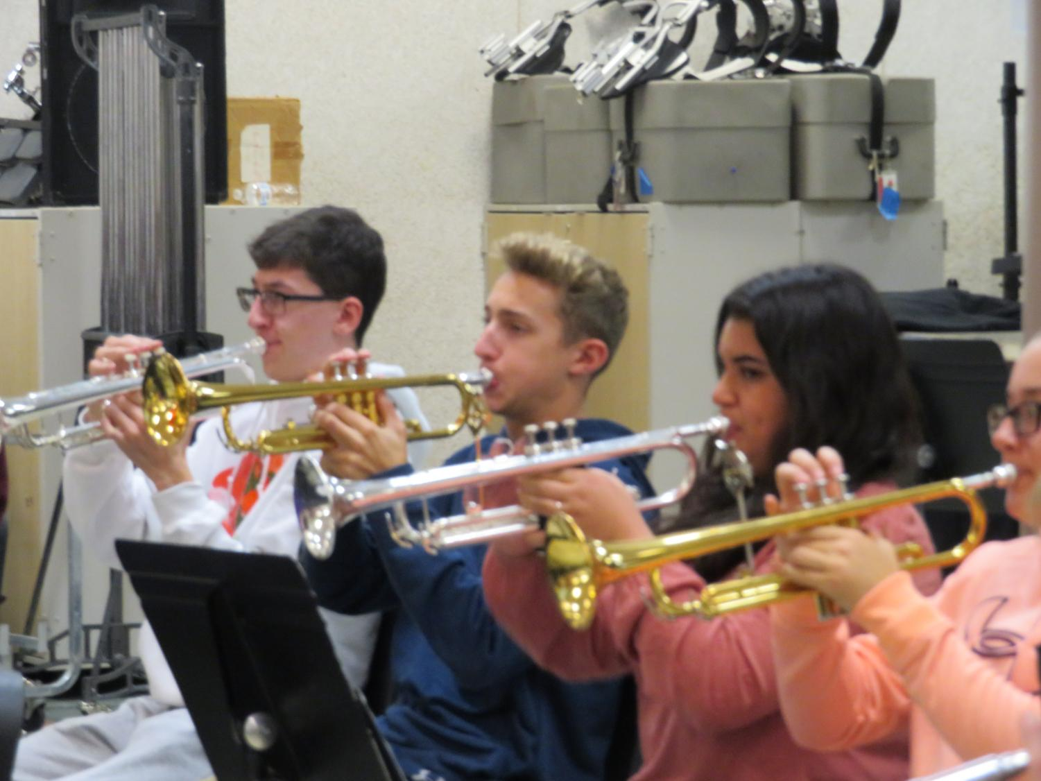 Senior Ryan Cullen and juniors Brandon White and Amara Cote practice their halftime music in band class.