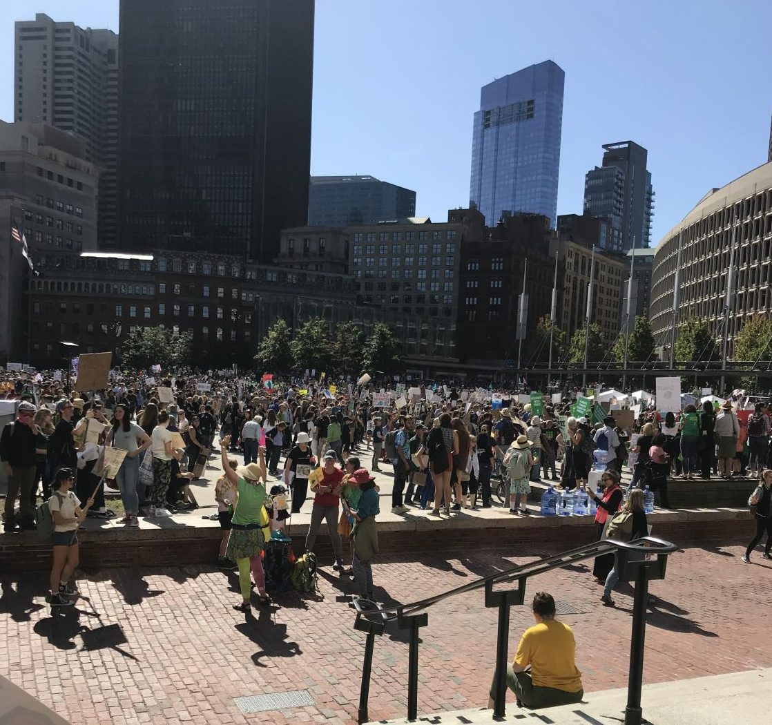 Protesters gather in Boston with their signs to protest the change in climate.
