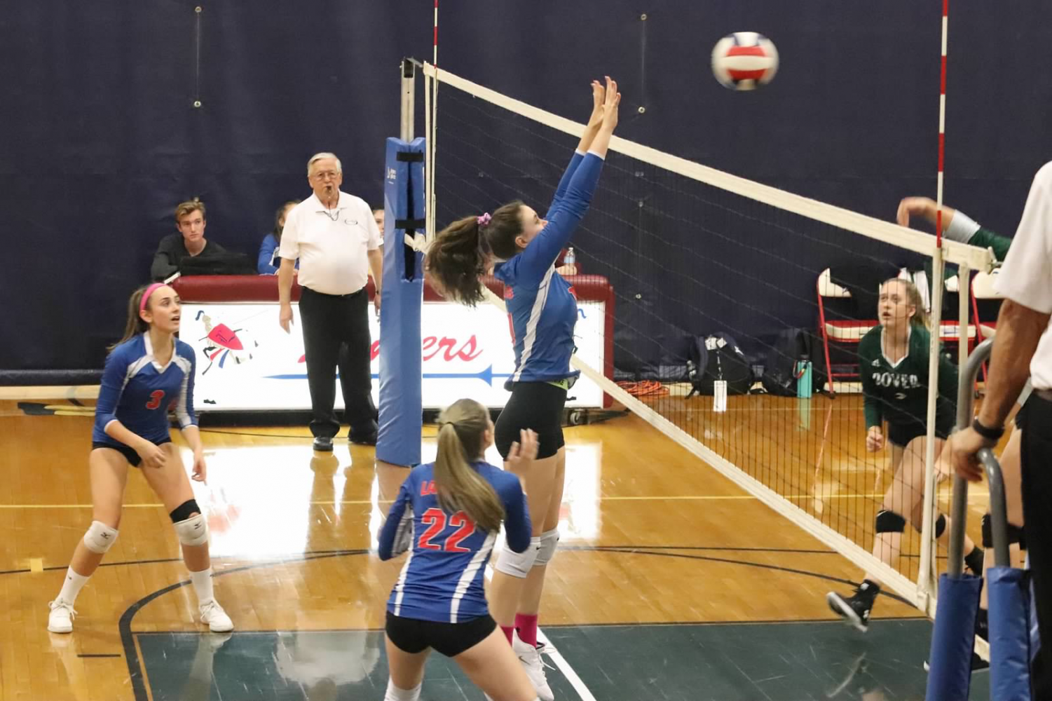 Junior Katrina King blocks a strong hit against Dover volleyball team.