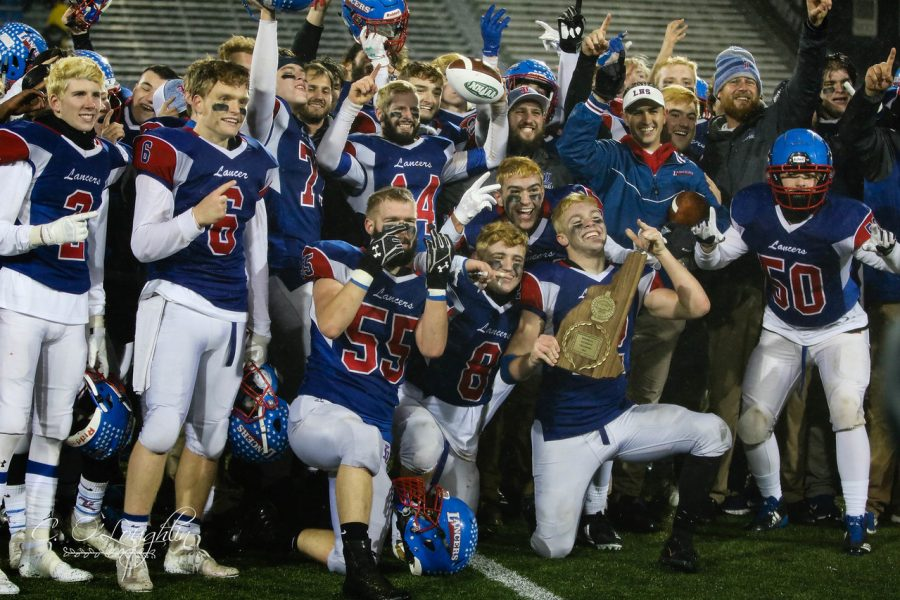 Senior+running+back+Jeffery+Wiedenfeld+holds+the+championship+plaque+while+his+teammates+celebrate+with+him.+The+Lancers+won+the+Division+One+State+Championship+game+21-10+over+Exeter.