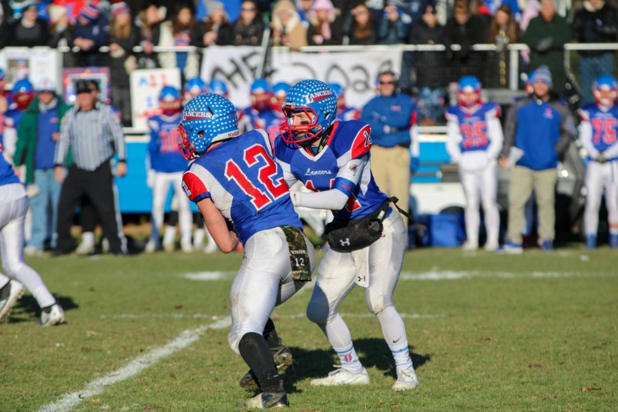 Quarterback+Jake+McEachern+hands+the+ball+off+to+running+back+Jeff+Wiedenfeld.+The+Lancers+defeated+Salem+in+the+Division+One+Semifinals+and+advanced+to+the+state+championship.