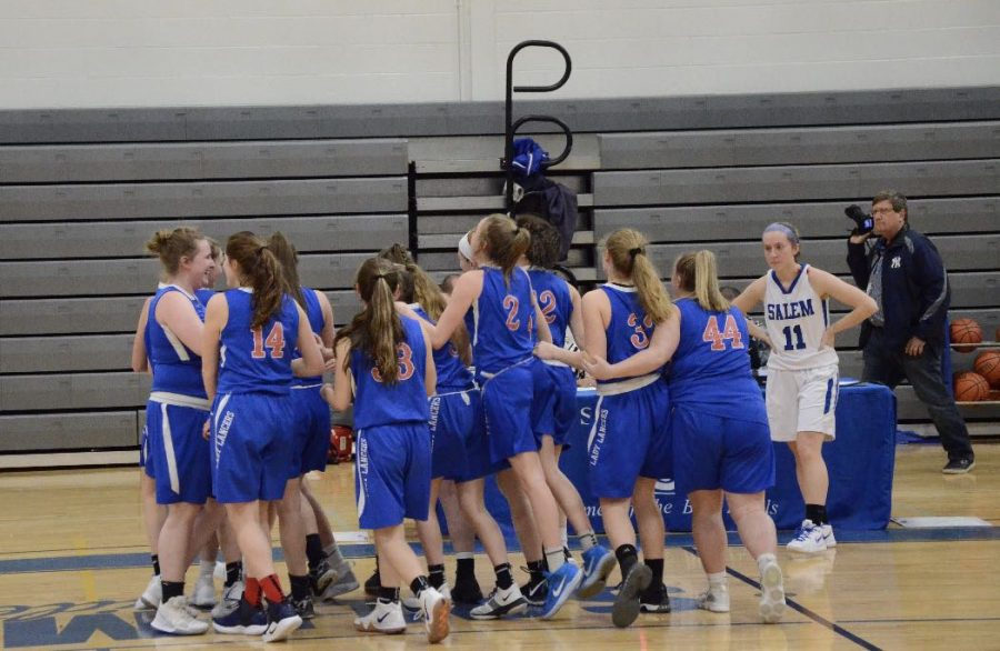 The+girls+stand+in+a+huddle+as+they+prepare+for+their+game+against+the+Salem+Blue+Devils.+