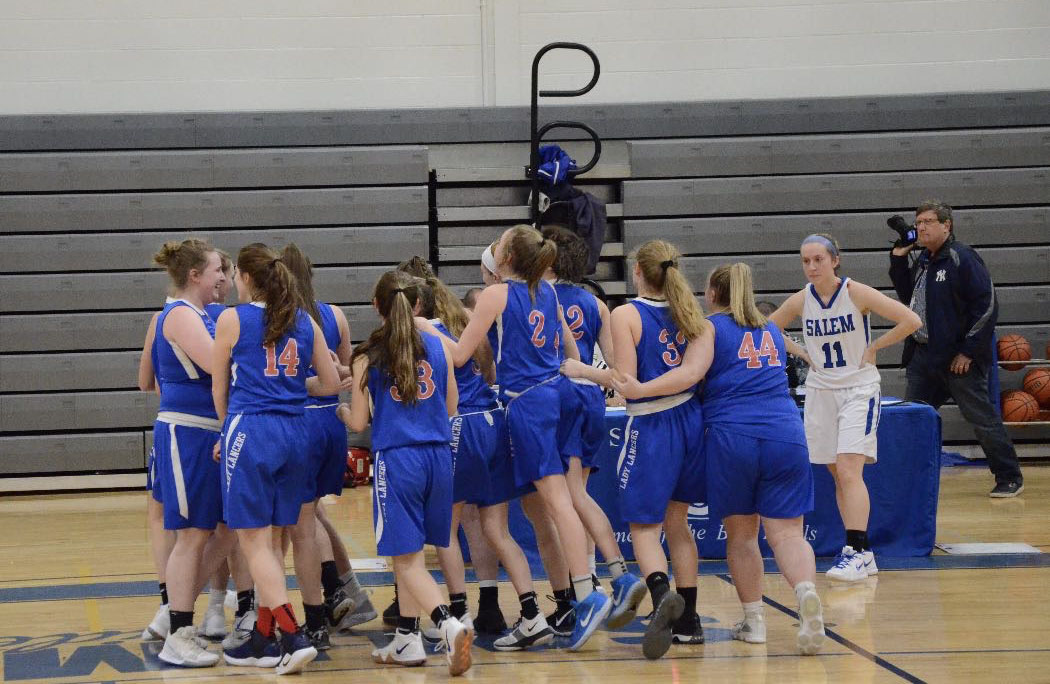 The girls stand in a huddle as they prepare for their game against the Salem Blue Devils.
