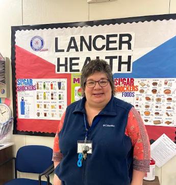 LHS Nurse Mrs. Cullen stands in front of Lancer Health bulletin board in the school nurse office.