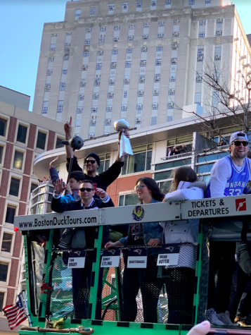 Tom Brady carrying the Lombardi trophy during the Super Bowl parade in Boston.