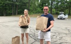 "Two volunteers from Londonderry Christian Church help bring bags out to the families in need during their ""every two week"" pick up drive-thru on Thursdays."