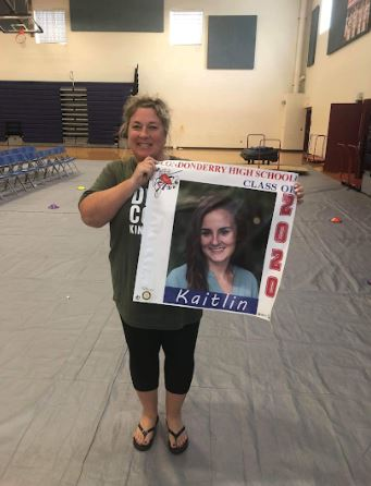 House 4 Assistant Principal Ms. Sullivan poses with a graduating seniors banner that was coordinated by the Rotary Club and hung on Mammoth Road.