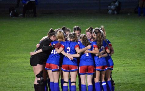 Girl's soccer huddles together before the Mack Plaque game.