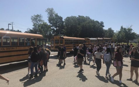 Class of 2023 socialize in front of buses on their orientation day in 2019.
