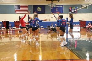 The volleyball team throws their hands up after winning a point.