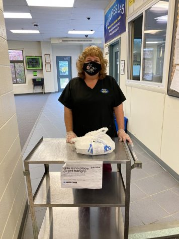 Cafeteria staff member Laura Francis gives out the pre-order meals for the E period lunch. Every lunch is packaged with the name of the student on the bag, making it easy for people to find their meals.