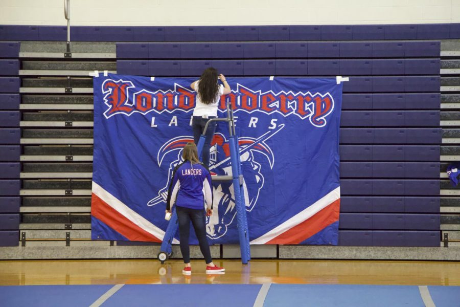 "Senior Amara Cote sets up a ""Londonderry Lancers"" banner in preparation for the pep rally. Photo by Sean O'Mara"