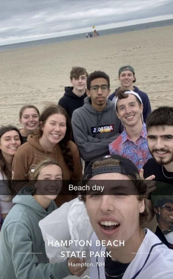 APES students stand on the beach after hours of picking up trash on the shoreline.