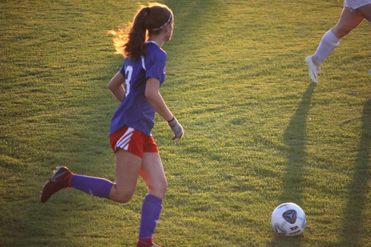 Sophomore Ashley Manor goes head to head in the recent game against Dover. Manor helps lead the team to a 5-1 win.